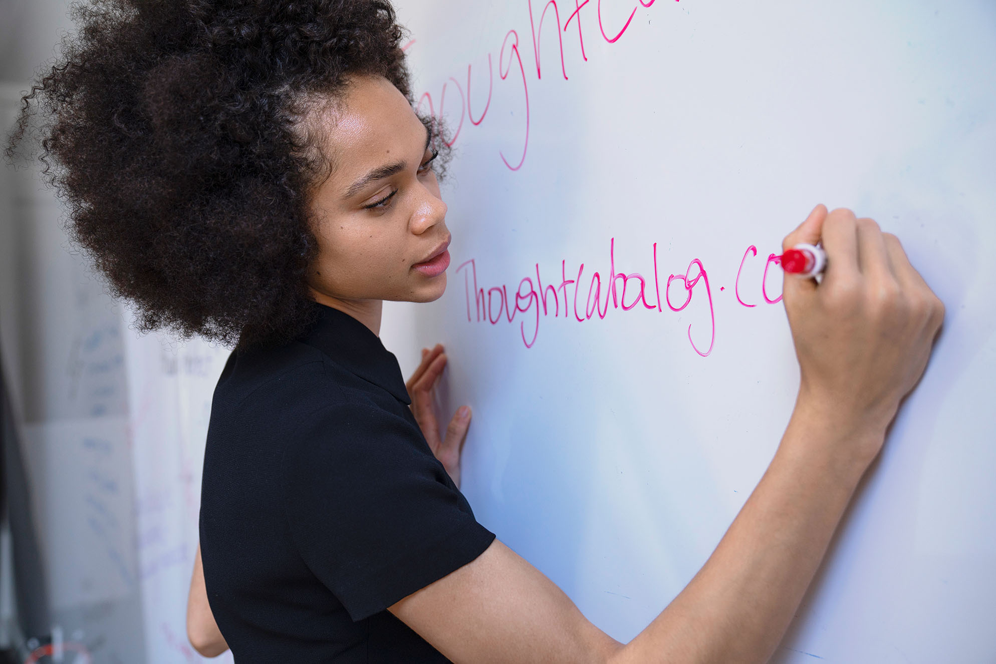 A woman uses a whiteboard during a meeting.
